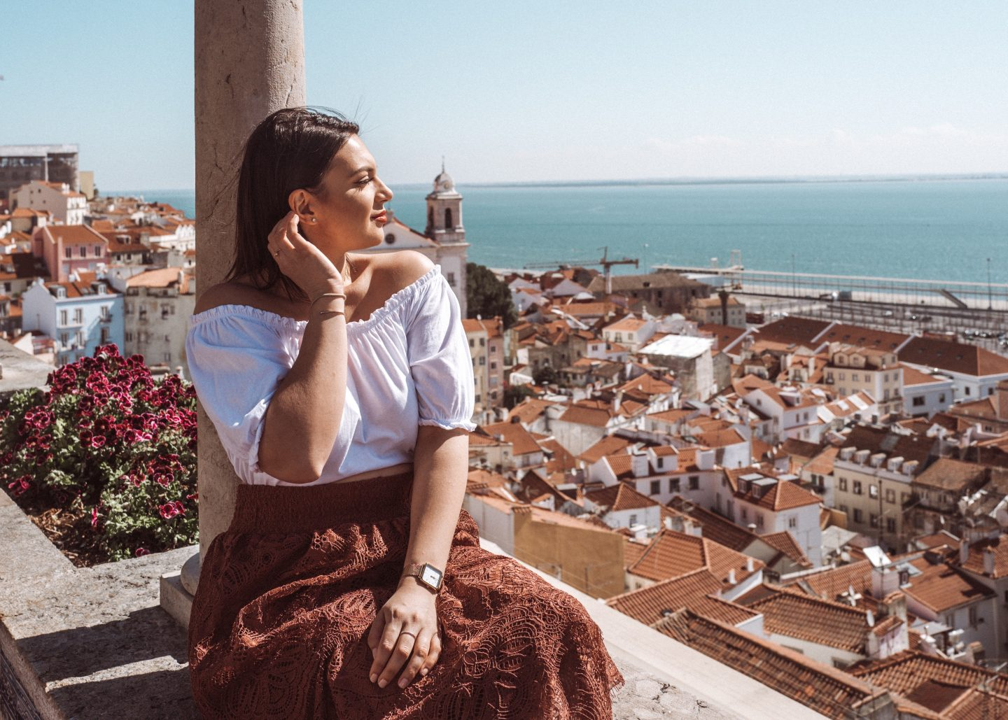 Mihaela sitting on a terrace overlooking Lisbon rooftops and the water